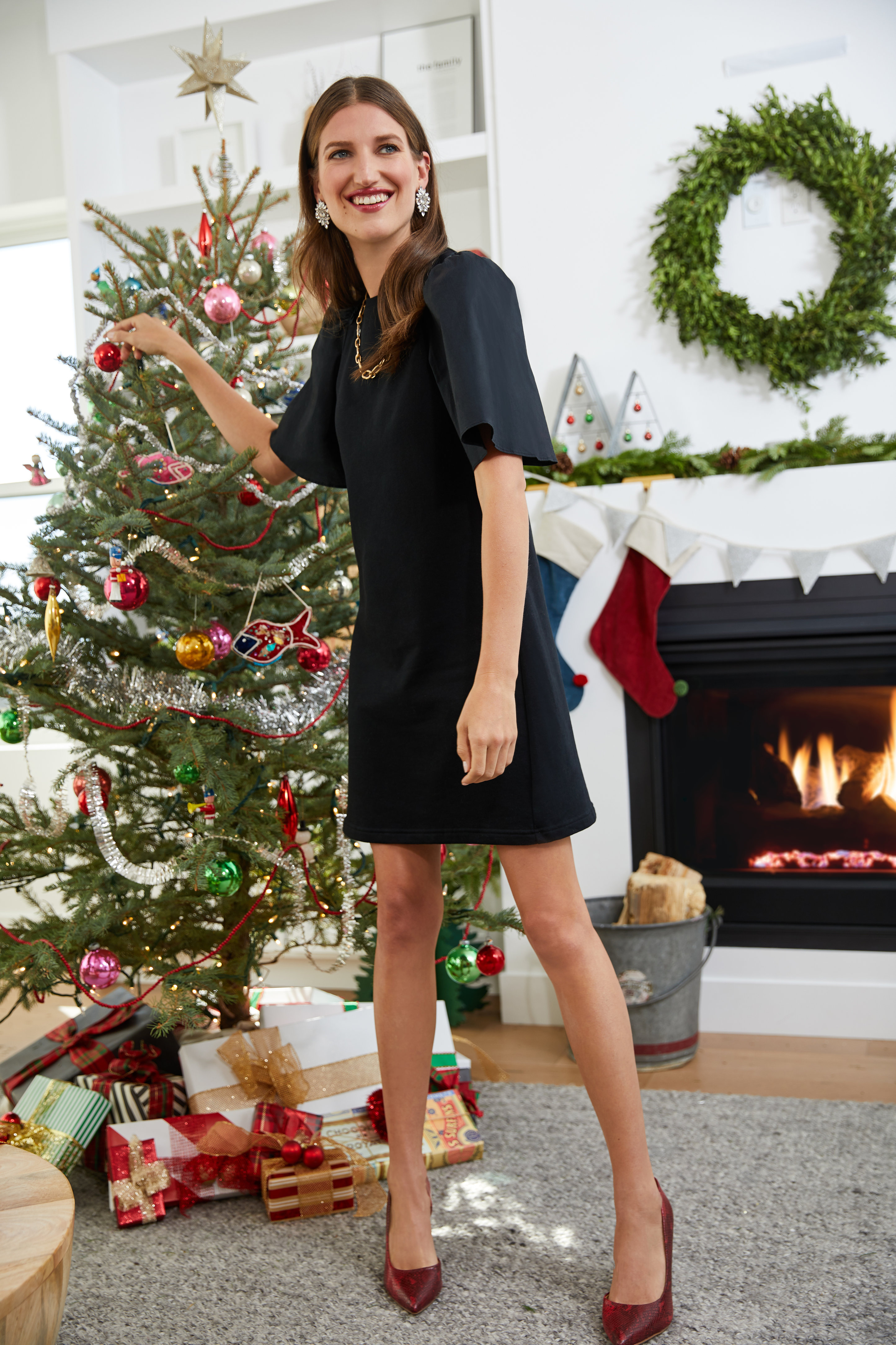 Woman In Black Dress Next To Christmas Tree